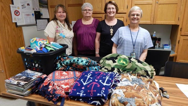 Members of the Shawneetown UDC Chapter 2706 recently traveled to the Veterans Hospital in Fayetteville, where they donated an assortment of handmade blankets, personal-care items and magazines and visited with veterans. Shown are, from left, Kathy Huff, Virginia Griffin and Betty Morrow of the UDC and a representative of the Veterans Hospital.