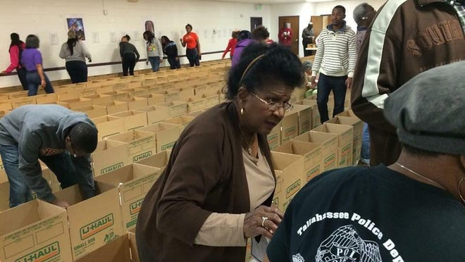 Dorothy Bethea, a church volunteer, prepares a Thanksgiving basket for a needy family.