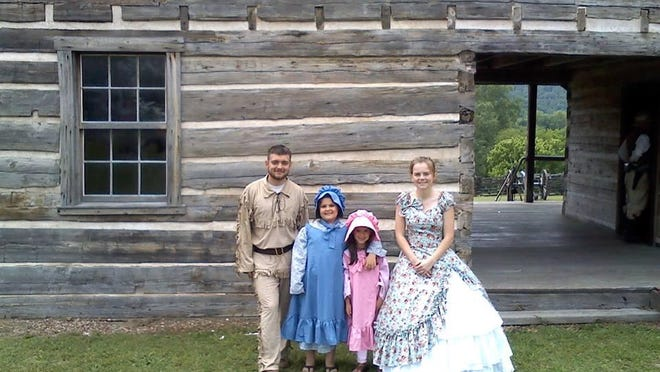 A pioneer family is portrayed at the Wolf House as part of the Norfork Pioneer Days celebration.