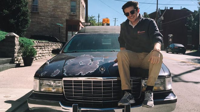 """Grant Webster sits atop the """"Helpful Hearse."""""""