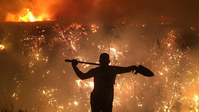 Joe Solf walks away from the flames in the Lodge Pole Complex Fire about 1:30 a.m. on Friday. The fire had just crossed the river into Petroleum County. It is now only 5 percent contained.