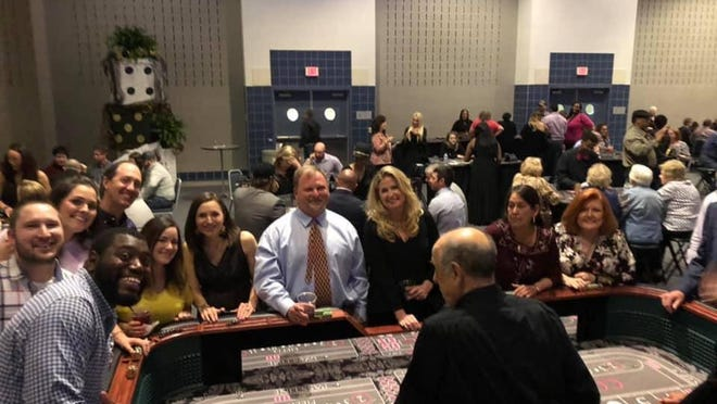 Guests gather around the craps table one of the previous Casino Nights at the Ardmore Convention Center. The Family Shelter has postponed this year's fundraiser until Sep. 4.