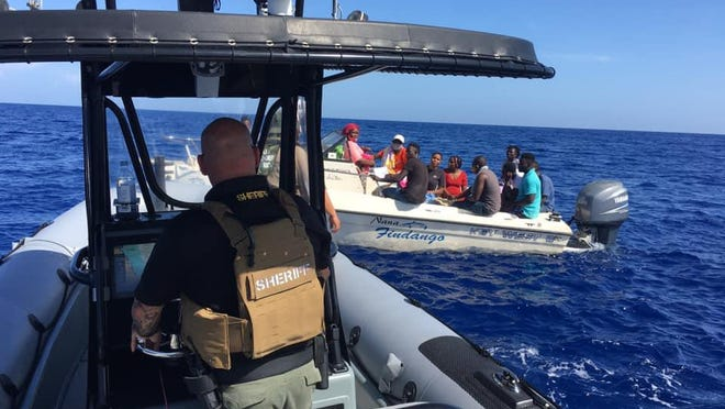 A Martin County Sheriff's Office deputy approaches a boat filled with migrants who were stranded at sea on Friday, July 3, 2020.