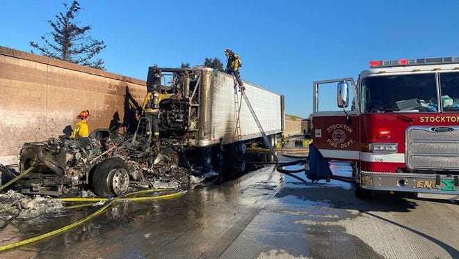 Stockton Fire Department firefighters inspect what's left of a big rig that caught fire late Sunday afternoon along northbound Interstate 5 in Stockton, tying up traffic for hours. The driver escaped unharmed.