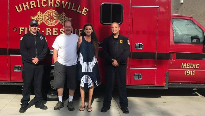 Marsha Civiello and her husband Rocky visited the Uhrichsville Fire Department on Wednesday to thank those who responded after she suffered cardiac arrest in May. The couple is shown with firefighter-paramedic Zach Lynch (left) and Capt. Wes Dillon.