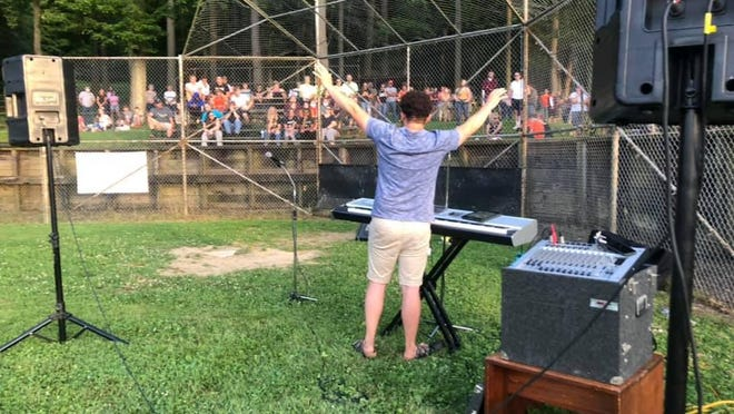 Dan Bias of Newcomerstown is pictured helping lead songs at a prayer vigil held at Cy Young Park on Tuesday evening. He was joined by his wife, Kristen, who took this picture.