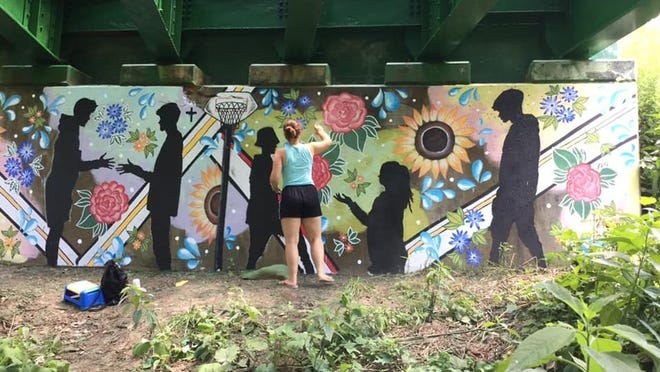 """Natalie Norris puts the finishing touches on the mural that she painted beneath a bridge in Almond. Norris said she wanted to add a """"hidden gem"""" to her hometown."""