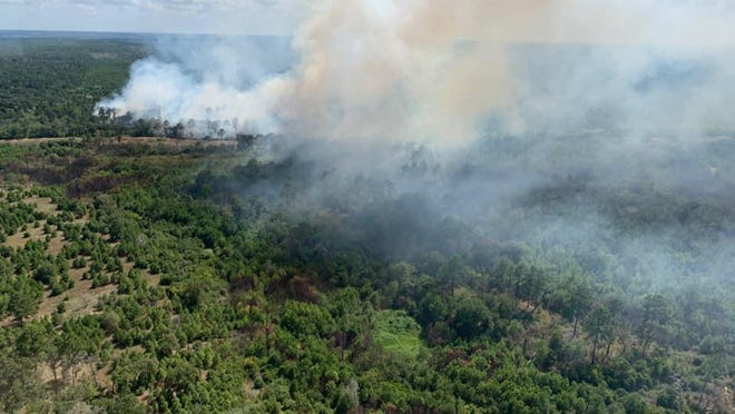 A wildfire in Bastrop State Park torched 27 acres Monday. State and federal firefighters were continuing fire containment work Tuesday as they let the fire burn itself out. Smoke is expected to continue from the fire for several days, officials said.