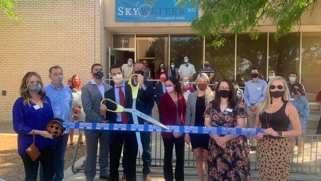 Ribbon Cutting - Skywriter MD, 1921 Broadway. Holding scissors: Dr. Brian Gill, board member. Holding ribbon - Chamber Ambassadors Katie Schafer, left, and Amy Stephens. Also pictured: COO Cameron Ramirez, Director of IT Roger Rue, President & CEO Tracy Rue, VP of Administration Elaine Widner, VP of Sales & Marketing - Amanda Stacy, Skywriters and other Chamber Ambassadors.