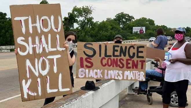 Protesters stand along the Old Iron Bridge in Bastrop on Sunday to protest the death of George Floyd at the hands of a Minneapolis police officer.