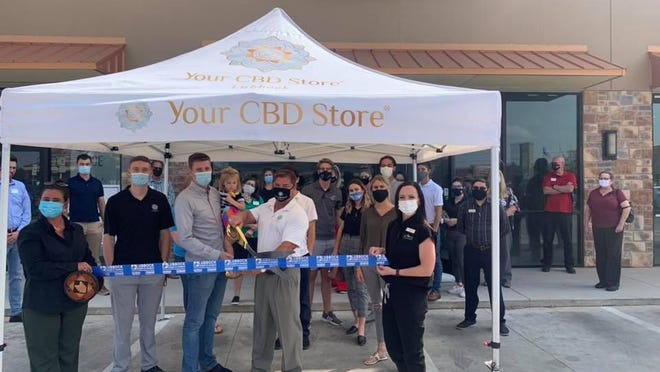 Ribbon cutting - Your CBD Store, 5207 98th St. Ste. 200.  Holding scissors: owners Jon Lobough and Tim Smyrson.  Holding ribbon: Chamber Ambassadors Shannon Younger, left, and Amy Franks. Also pictured: other staff, family, friends and Chamber Ambassadors.