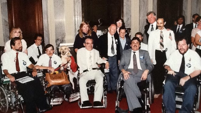 Paul Spooner is seen here with his service dog Klister (second to left) and a group of other disability leaders at a reception held by Sen. Ted Kennedy after the signing of the Americans with Disabilities Act in 1990.