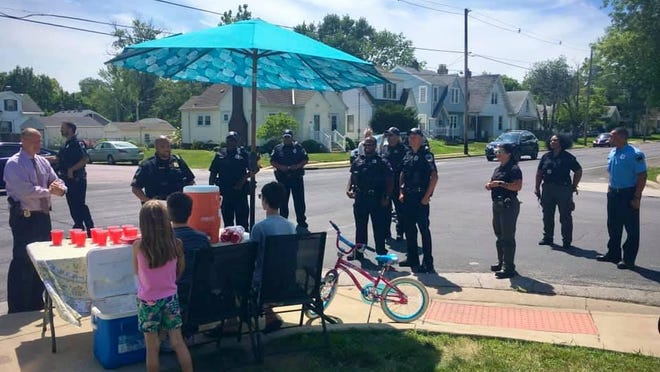Peoria Police Chief Loren Marion, far left, was among officers who on Tuesday visited an East Bluff lemonade stand that was robbed last week.