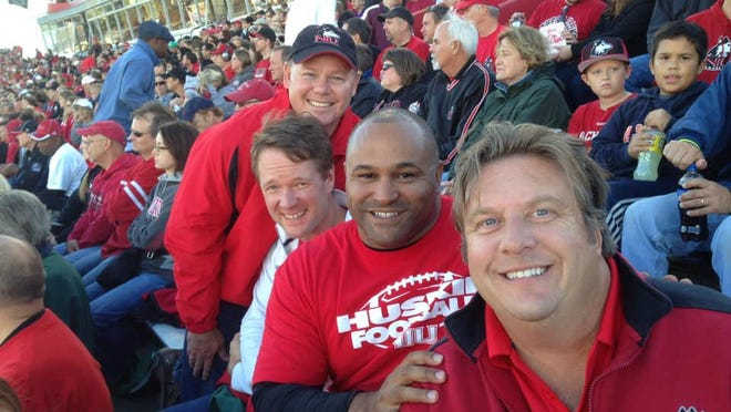 John Ivanic, front, a former record-setting kicker at Northern Illinois University, died Monday. After graduation, Ivanic worked as an anchor at 13 WREX in Rockford.