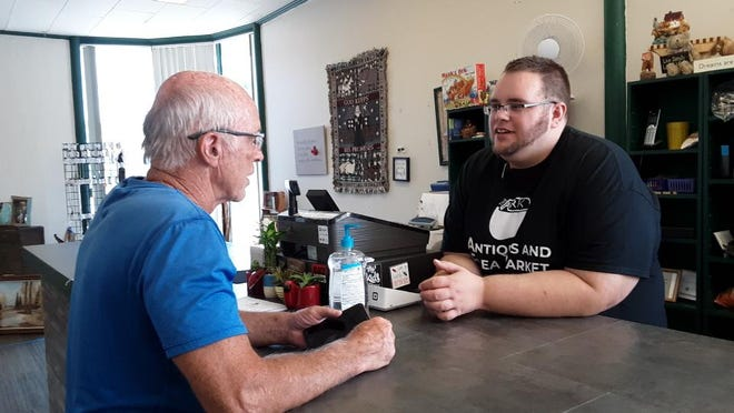 Ben Coffey, right, speaks with customer RIck Tease at the new The Ark Antiques and Flea Market in downtown McPherson.