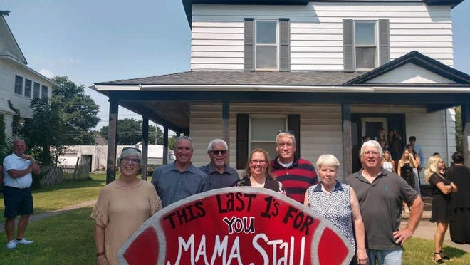 Mary Lynn Patterson, Bob Stallbaumer,, Roger Stallbaumer, Misty Barnum, Scott Stallbaumer, Terri Cornejo and Joe Stallbaumer stand behind a sign for Mama Stall outside the old Stallbaumer house.