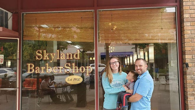 Caroline and Mikey Bellamy, along with their son Charles, pose for a photo outside of Skyland Barber Shop in May. The Hendersonville natives have officially reopened the downtown staple.