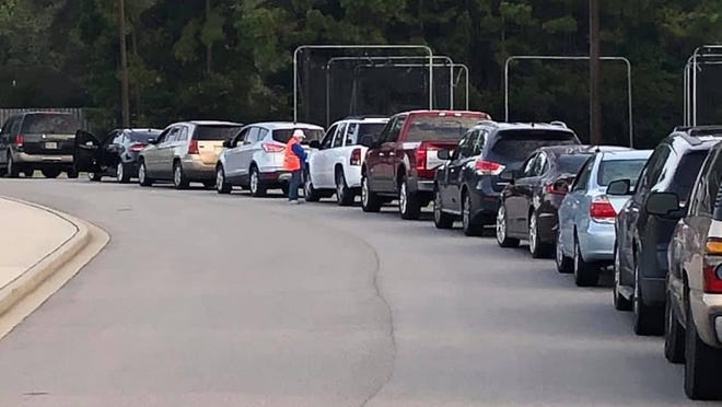 People in a line of vehicles to receive free food from Manna House on Sept. 30.