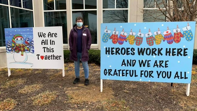 Local artist and downtown business owner Carolyn Stich poses with two of the six large signs she donated to Holland Hospital to acknowledge the hard work of medical professionals during the pandemic.