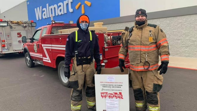 Jonesville firefighters pose for a photograph next to a Toys for Tots donation box Saturday at Walmart.