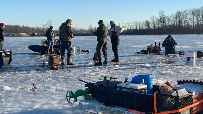 A conservation officer with the Michigan Department of Natural Resources checks fishing licenses Jan. 9 at Baw Beese Lake in Hillsdale.
