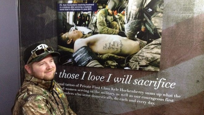 Army Pfc. Kyle Hockenberry signs a now-famous photo of him as he was being airlifted to a field hospital in Afghanistan. The tattoo on his side reads: For those I love, I will sacrifice. The photo is part of the Never Forget Mobile Exhibit.