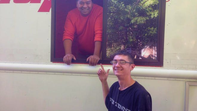 Chumpot Ratanawong, owner of Hanuman Express, stands in his food truck with Tom Schrader, who helped Ratanawong renovate the mobile restaurant.