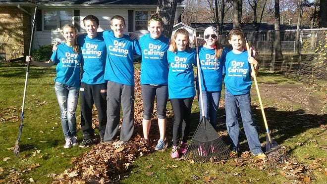 Youths from John Edwards High School volunteer to rake a yard in Port Edwards.