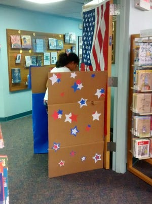A child votes for president during the Kid's Vote mock election.