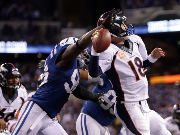 Denver Broncos quarterback Peyton Manning, #18, is hit from behind by former teammate Indianapolis Colts Robert Mathis, #98, Sunday, October 20, 2013.