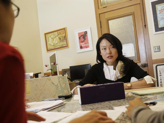 City supervisor Jane Kim talks to members of her staff as she is interviewed at City Hall in San Francisco. Kim is calling for a tax on companies that automate jobs once held by people.