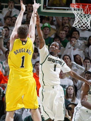 Michigan's Stu Douglass shoots over Michigan State's Kalin Lucas in U-M's 61-57 win on Jan. 27, 2011, in East Lansing.