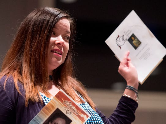 Brandy Mayo, of Nashville, holds up the funeral programs
