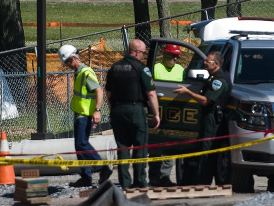University of Vermont police speak to each other while construction workers stand in the background June 30 at UVM campus.