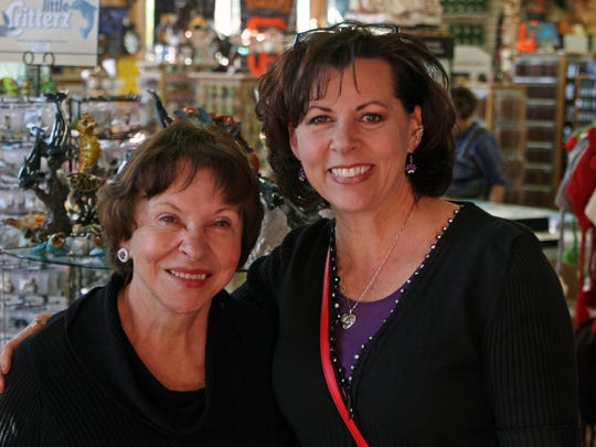 Sally Elves, left, and Sherri Tuioti pose in the center of Harbor House Gifts