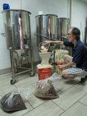 Jeff Robinson, owner and brewer at Third Monk Brewing Company in South Lyon, crushes grain for a batch of stout.