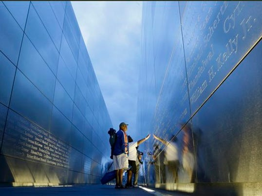 "Jimmie Corley and wife, Rosiland Corley look for the name of a family member on the ""Empty Sky"" memorial to New Jersey's victims of the Sept. 11, 2001 terrorist attacks early Friday, Sept. 11, 2015, in Jersey City, N.J.  Victims' relatives began marking the 14th anniversary of Sept. 11 in a subdued gathering Friday at ground zero, with a moment of silence and somber reading of names. (AP Photo/Mel Evans)"