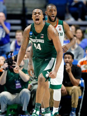 Michigan State freshman Nick Ward celebrates a basket in front of Miami forward Kamari Murphy, rear, in the first half Friday night in Tulsa, Oklahoma. Ward finished with 19 points and seven rebounds.