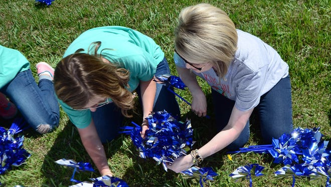 Didi Ellis with Kids Hub Child Advocacy Center, right, and Anna Claire Mercer with Southern Miss Kappa Delta Sorority place a pinwheel garden in front of Pine Belt Ford in Purvis to raise awareness for child abuse prevention.