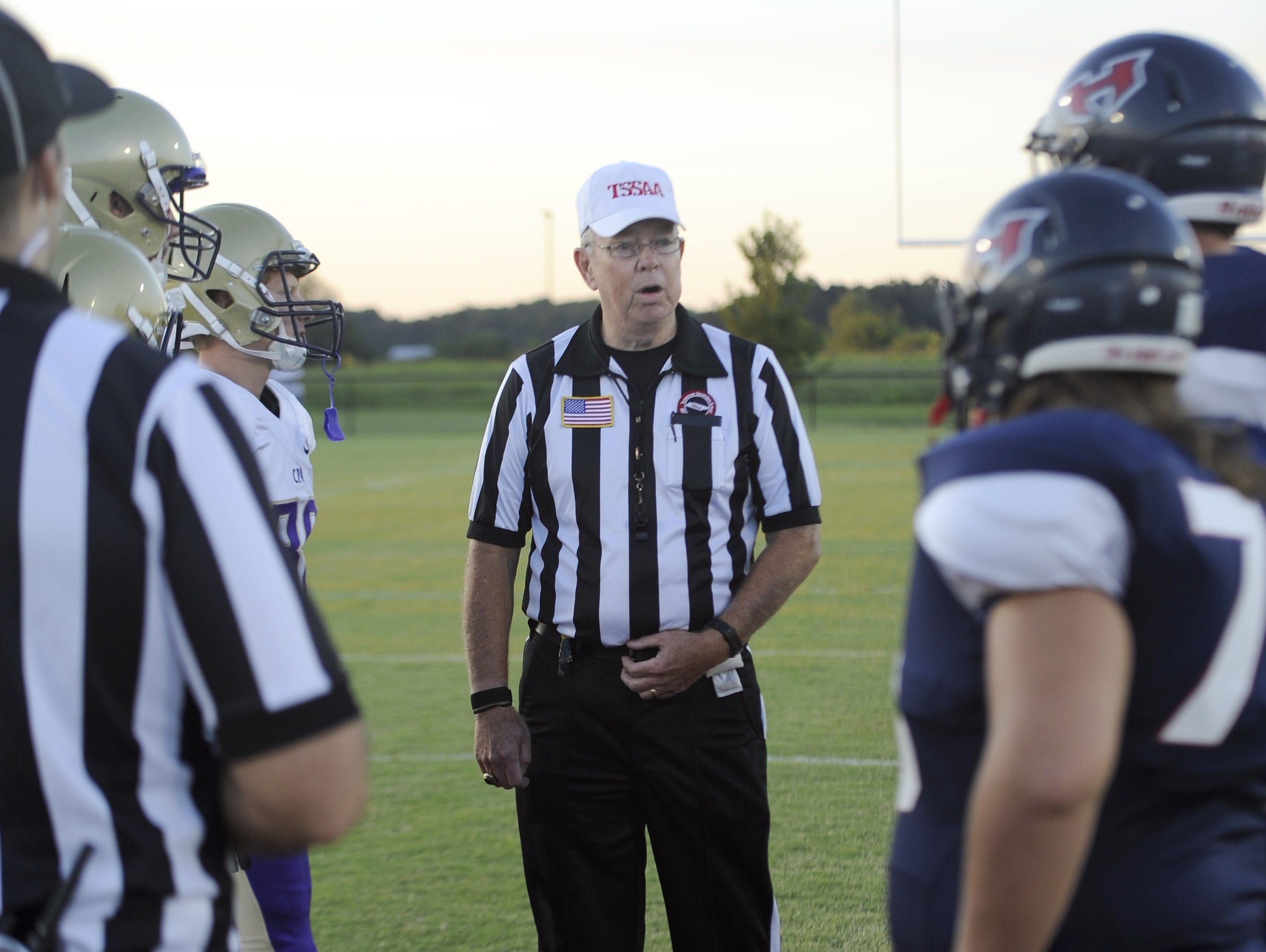 North Middle Football Officials Association referee Jody Swearingen talks with the captains prior to kickoff of last Friday's Christ Presbyterian Academy/White House Heritage game.