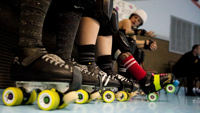 Team members of Black Rose Rollers wait on the bench on Sunday Feb. 23, 2014 during their bout against Assault City at Magic Elm Skateland in Hanover.  Shane Dunlap - The Evening Sun