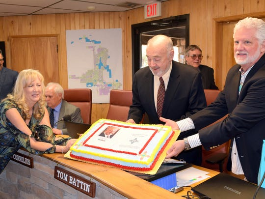 Mayor Pro tem Lynn Crawford and administrative assistant Utahna M. Dominguez help outgoing mayor Tom Battin, center, hold up his cake. In the background are from left, councilors Rifle Salas, Tim Coughlin and John Cornelius.