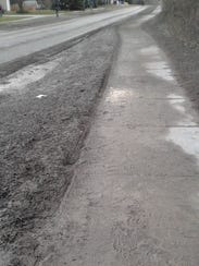 A sidewalk along the west side of Peters Road is caked