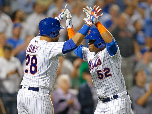 New York Mets on-deck batter James Loney (28) greets Yoenis Cespedes (52) after Cespedes hit a two-run home run off St. Louis Cardinals starting pitcher Adam Wainwright during the seventh inning of a baseball game, Wednesday, July 27, 2016, in New York. (AP Photo/Kathy Willens)
