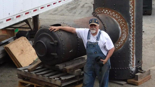 Carl Wassink is shown with the boiler of Climax A 313 in Alaska, before the boiler and other steam engine parts were loaded for shipment home to Corry.