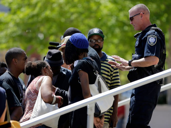 A member of the Federal Protective Service asks demonstrators to stay off the steps leading to the Thomas F. Eagleton federal courthouse during a protest in St. Louis. About 100 protesters marched from city hall to the courthouse as they continue to press for broader reforms to local and federal law enforcement following the shooting death of Michael Brown by police.