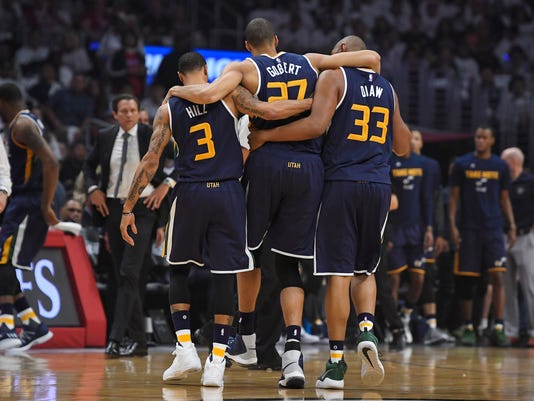 Utah Jazz center Rudy Gobert, center, is helped off the court by center Boris Diaw, right, and guard George Hill, left, as coach Quin Snyder watches after Gobert injured his knee during the first half in Game 1 of an NBA basketball first-round playoff series against the Los Angeles Clippers, Saturday, April 15, 2017, in Los Angeles. (AP Photo/Mark J. Terrill)
