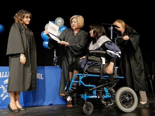 Del Valle senior Jackie Avalos crosses the stage to receive her diploma during a special graduation ceremony Friday.