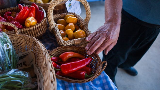 Tom Huffer gestures to some of the sweet peppers at his booth while talking with a customer at the Waynesboro Farmers Market on Saturday, Aug. 22 2015.