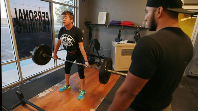 Paula Powell performed dead lifts Friday as trainer Jonathan Ramos observed Friday at Sho Offz Fitness, 12,320 Lorenzo Ruiz.